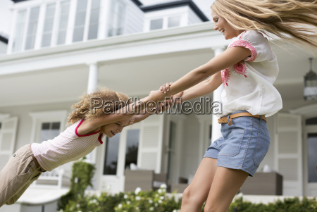 mother and daughter playing outside house