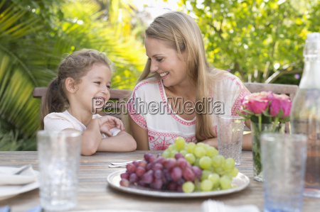 mother and daughter smiling at table