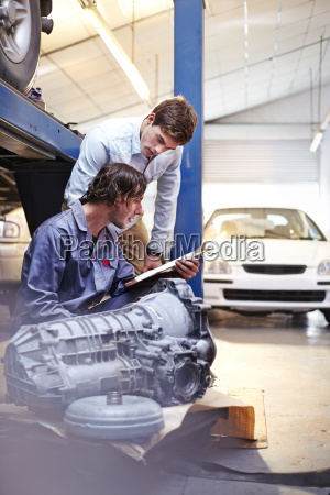 mechanic with clipboard talking to customer