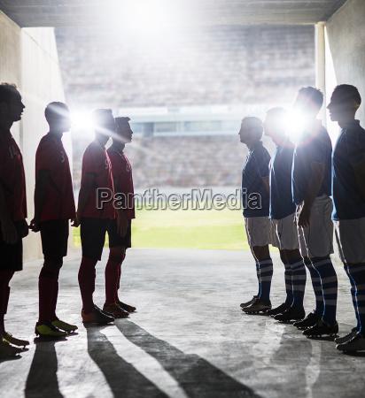 silhouette of soccer teams greeting in