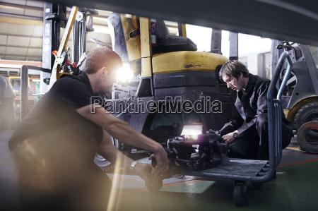 mechanics fixing forklift in auto repair