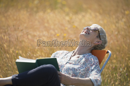 senior woman reading book and laughing