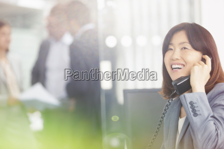 smiling businesswoman talking on telephone in