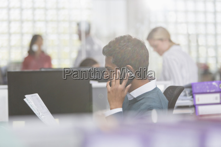 businessman with paperwork talking on cell