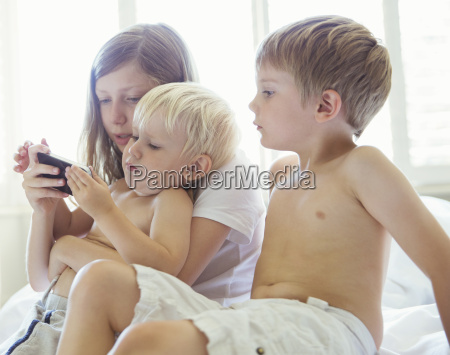 children using cell phone together