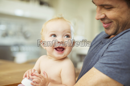 father holding baby in kitchen