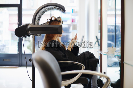 woman sitting under dryer texting with