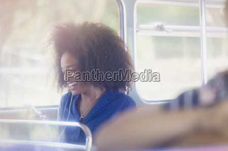 smiling woman with afro texting with