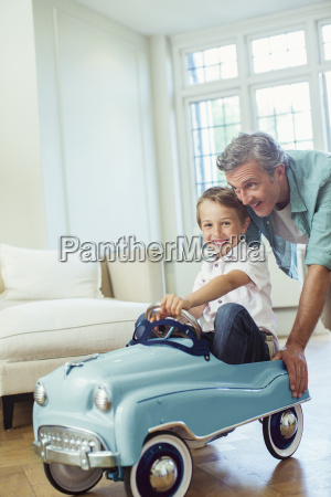 father pushing son in toy car