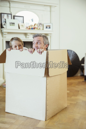 father and son playing in cardboard