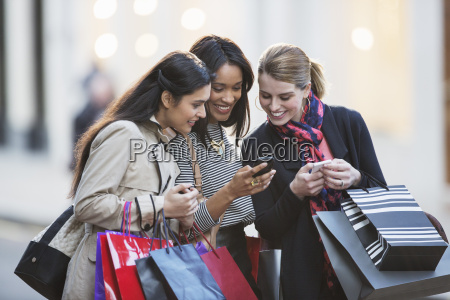 women looking at cell phone on