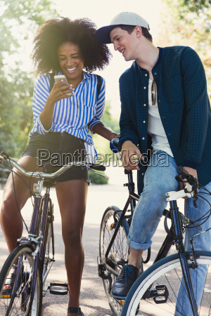 friends on bicycles texting with cell