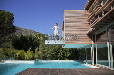 woman standing on balcony over swimming