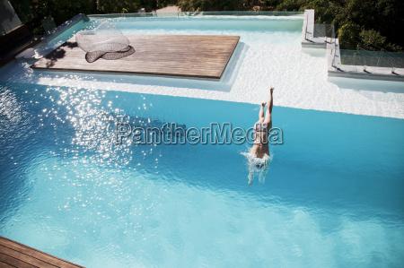woman diving in luxury swimming pool