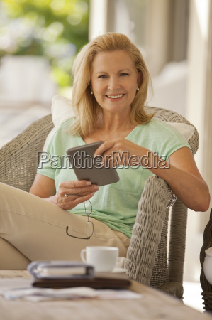 portrait of smiling woman using digital