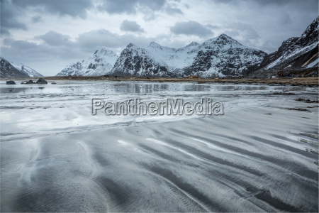 snow covered mountains behind cold beach