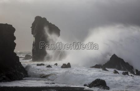 ocean waves crashing against rock formations