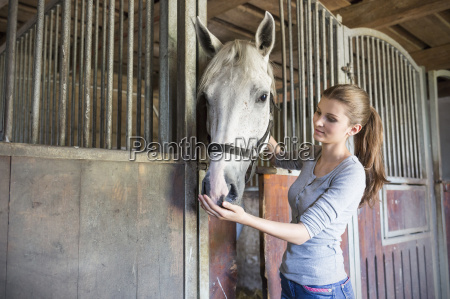 woman feeding horse at stable stall