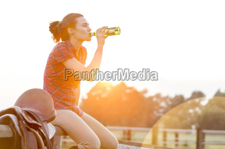 woman drinking water next to saddle