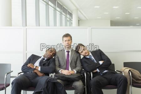 businessmen sleeping in waiting area