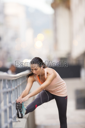 woman stretching before exercising on city