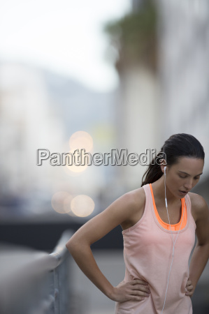 woman resting after running on city
