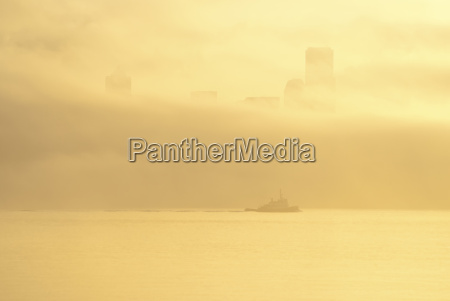 silhouette of tugboat and fog over