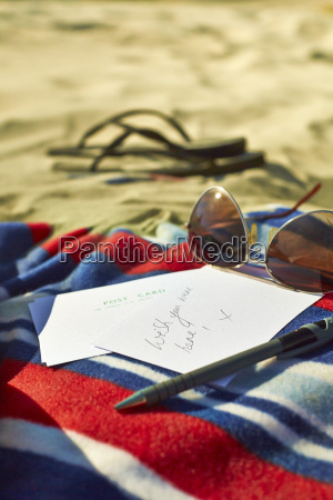 postcards sunglasses and sandals at beach