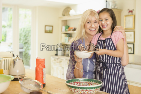 portrait smiling grandmother and granddaughter baking