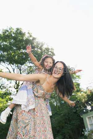 portrait carefree mother piggybacking daughter with