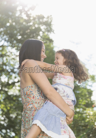 affectionate mother holding and hugging daughter