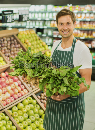clerk carrying basket of produce in