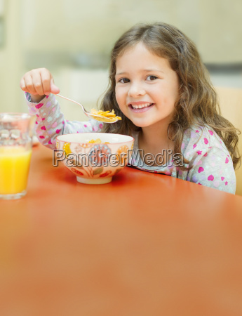 portrait smiling girl eating cereal at