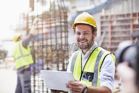 portrait confident construction worker with digital