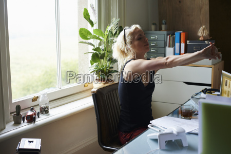 young woman stretching arms at desk