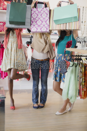 women holding shopping bags in clothing