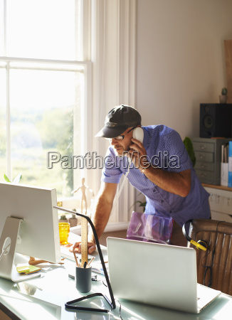 man talking on telephone and using
