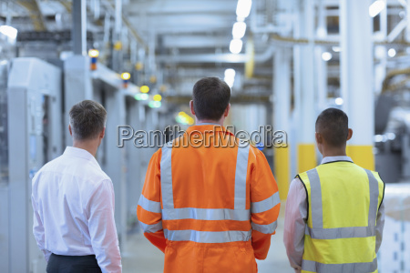 workers and supervisor standing in factory