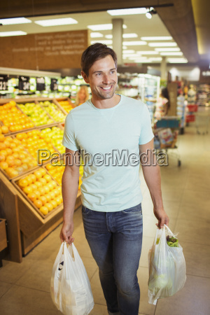 man carrying shopping bags in grocery