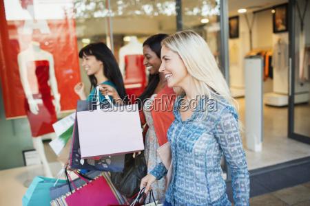 women carrying shopping bags in shopping
