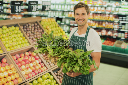 clerk carrying produce in grocery store