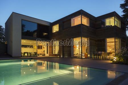 modern house and swimming pool illuminated