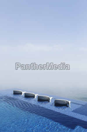 lawn chairs in infinity pool overlooking