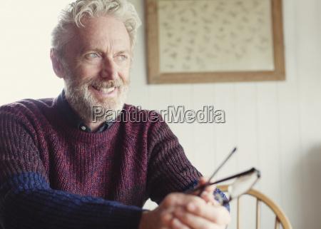 pensive senior man holding eyeglasses and