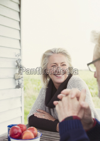 smiling senior couple talking at patio