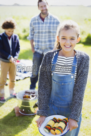 portrait smiling girl with vegetable skewers