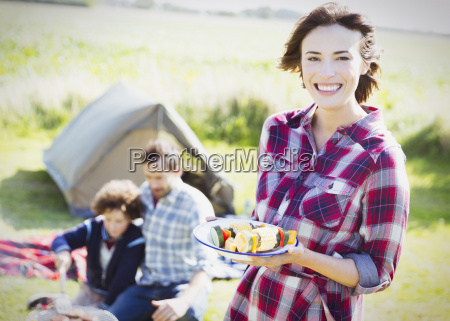 portrait smiling woman with vegetable skewers