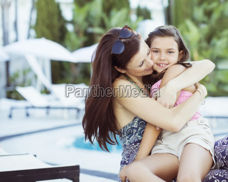 mother embracing her daughter on poolside