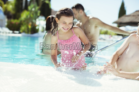 happy children splashing water in swimming