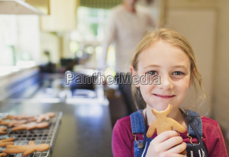 portrait smiling girl eating gingerbread cookie